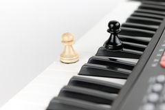 Two pawns on music keyboard. Black and white pawns on music keyboard royalty free stock photos
