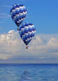 Two Peaceful Floating Hot Air Balloons. Two blue stripped hot air balloons floating over calm ocean and fluffy cloud skies Royalty Free Stock Image