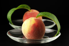 Two peaches. In glass saucers on black background Stock Photos