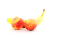 Two Peaches and Banana on White Royalty Free Stock Images