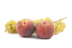 Two peaches and grapes branch on white. Background Royalty Free Stock Image