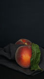Two peaches leaf with grey napkin dark Stock Images