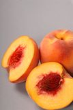 Two peaches, one cut in half Stock Image