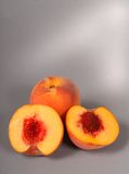 Two peaches, one cut in half Royalty Free Stock Image