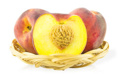 Two peaches and peach with a cut in the basket Royalty Free Stock Photography