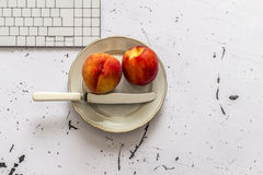 Two peaches in plate on office tabble, top view Stock Photography