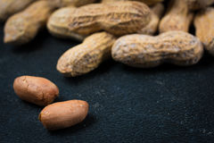 Two Peanuts without Shells Infront of a Pile of Peanuts Stock Image