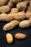 Two Peanuts without Shells Infront of a Pile of Peanuts Close Up Stock Photos