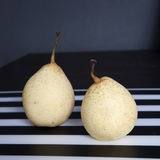 Two pears on a black and white striped napkin Royalty Free Stock Photography