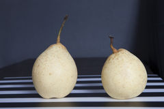 Two pears on black and white striped napkin Royalty Free Stock Images
