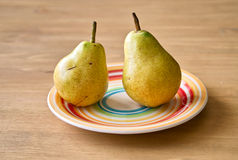 Two pears on color plate Royalty Free Stock Images