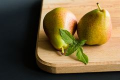 Two pears with fresh basil leaves on a wooden cutting board with black background stock image