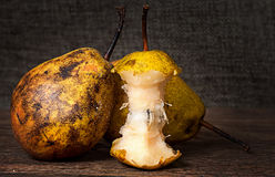 Two pears and stub standing on wooden table. Background sacking Royalty Free Stock Images