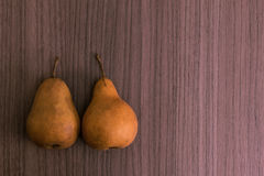 Two pears. Two succulent golden pears over wood background Royalty Free Stock Photo