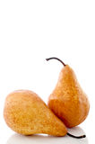 Two pears on a white reflective surface Royalty Free Stock Photos