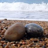 Two pebbles on beach. Two wet pebbles on an English beach with a wave breaking in the background Stock Photos