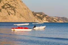 Two pedal boats pictured in Laganas bay at the golden hour. Kalamaki, Zakynthos. Greece. Two pedal boats  with Green flag pictured in Laganas bay at the golden royalty free stock photography