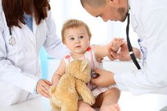 Two pediatricians are taking care of baby in hospital. Little girl is being examining by doctor with stethoscope. Health. Care, insurance and help concept Royalty Free Stock Photos