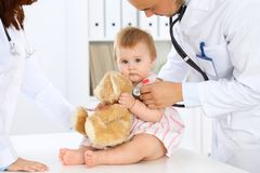 Two pediatricians are taking care of baby in hospital. Little girl is being examining by doctor with stethoscope. Health. Care, insurance and help concept Stock Photography