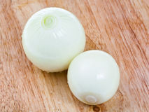 Two peeled onions bulbs on wooden board Royalty Free Stock Photo