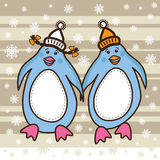 Two penguins dressed in hats walking together Royalty Free Stock Photography