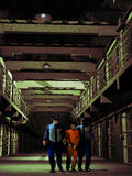 Prisoner custody. Two penitentiary guards, accompanying a prisoner in the corridor between the cells Royalty Free Stock Images