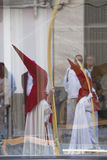 Two penitents reflected in a glass in a procession of holy week on Palm Sunday Royalty Free Stock Photo