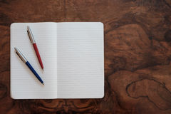 Two pens on a copy book isolated on wooden background Royalty Free Stock Image