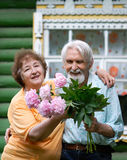 Two pensioners. Elderly husband and the wife hold flowers in hands and laugh and joke against the house Royalty Free Stock Photography