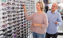 Two pensioners choosing sunglasses Stock Images