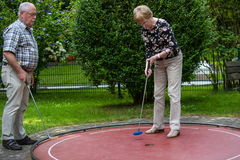 Two pensioners at a minigolf court playing minigolf. He is watch Royalty Free Stock Photography