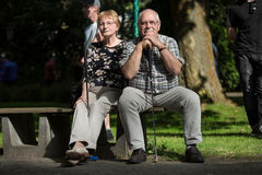 Two pensioners at a minigolf court are waiting on a park bench a Stock Photography