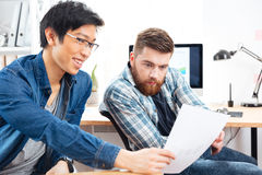 Two pensive men sitting and working with documents in office Royalty Free Stock Images