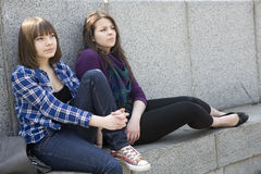 Two pensive teen girls sitting at river Stock Photos