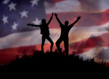Two people against the American flag Full length silhouette. Of a happy couple stand together on top of a mountain with their hands up, Man and woman on top of Stock Photo