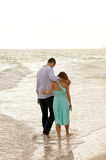 Two people arm in arm walking through the ocean. A couple of young adults walk through the water at the coastline of the gulf of mexico  in florida with their Royalty Free Stock Photography
