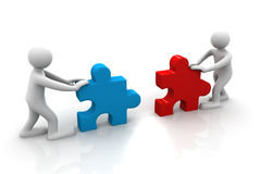 Two people assemble tow piece of a puzzle Royalty Free Stock Photo