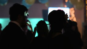 Two people within audience are dancing back to camera, man and woman moving to the music with masquerade masks on their stock video footage