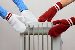 Two people bask near the oil cooler gloves Royalty Free Stock Photography