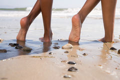 Two people on beach with crossed legs Royalty Free Stock Photo