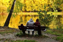 Two people on bench near lake in autumn day Royalty Free Stock Image
