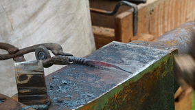 Two people in blacksmith forging red hot iron on anvil stock video footage