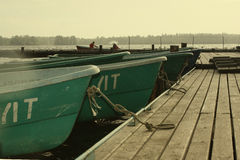 Two people in boat having moored to pier. Stock Image