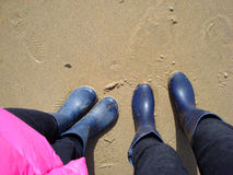Two people in boots on the beach Royalty Free Stock Images