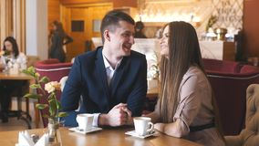 Two people in cafe enjoying the time spending with each other. Attractive young couple hanging out and talking while enjoying a cup of coffee at a restaurant stock video