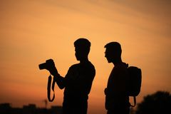 Two people with camera at sunset Stock Photo