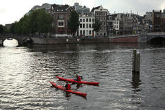 Two people on canoes in the Amstel River in Amsterdam stock images