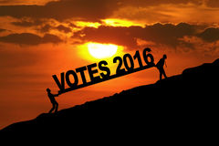 Two people carrying text of votes 2016 Royalty Free Stock Images