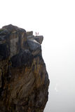 Two people on cliff side Stock Image