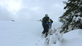 Two people climb in the snowy hill stock video footage